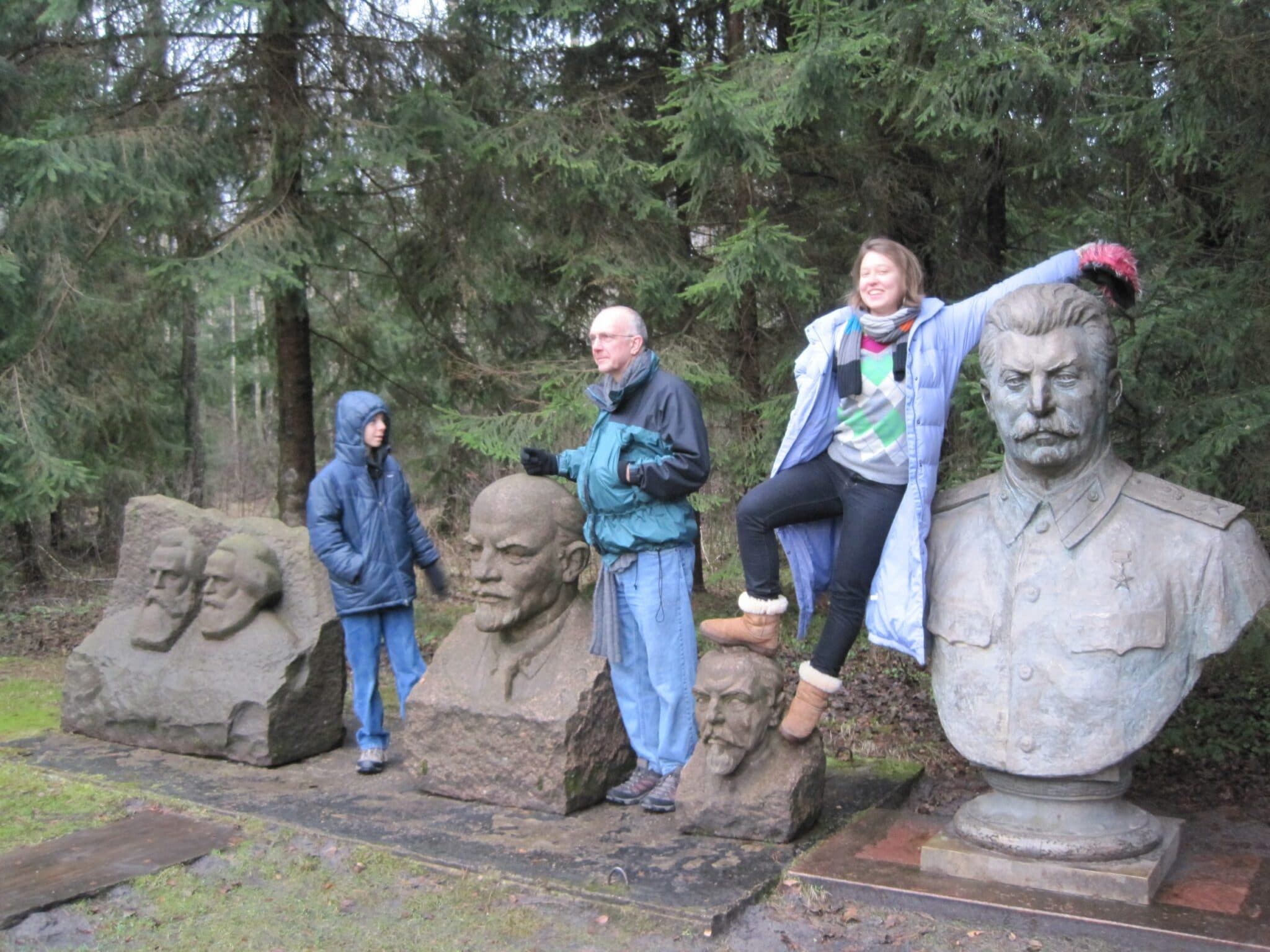 The author and family interact with statues of Marx, Engels, Lenin and Stalin that were previously located in the cities of Lithuania at Grutas park.