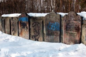 """Graffiti on headstones at Bródno cemetery. On stone slabs someone scribbled: """"Jews are shit,"""" """"SS."""" There are also drawings of swastikas, pigs and Stars of David hanging on gallows."""
