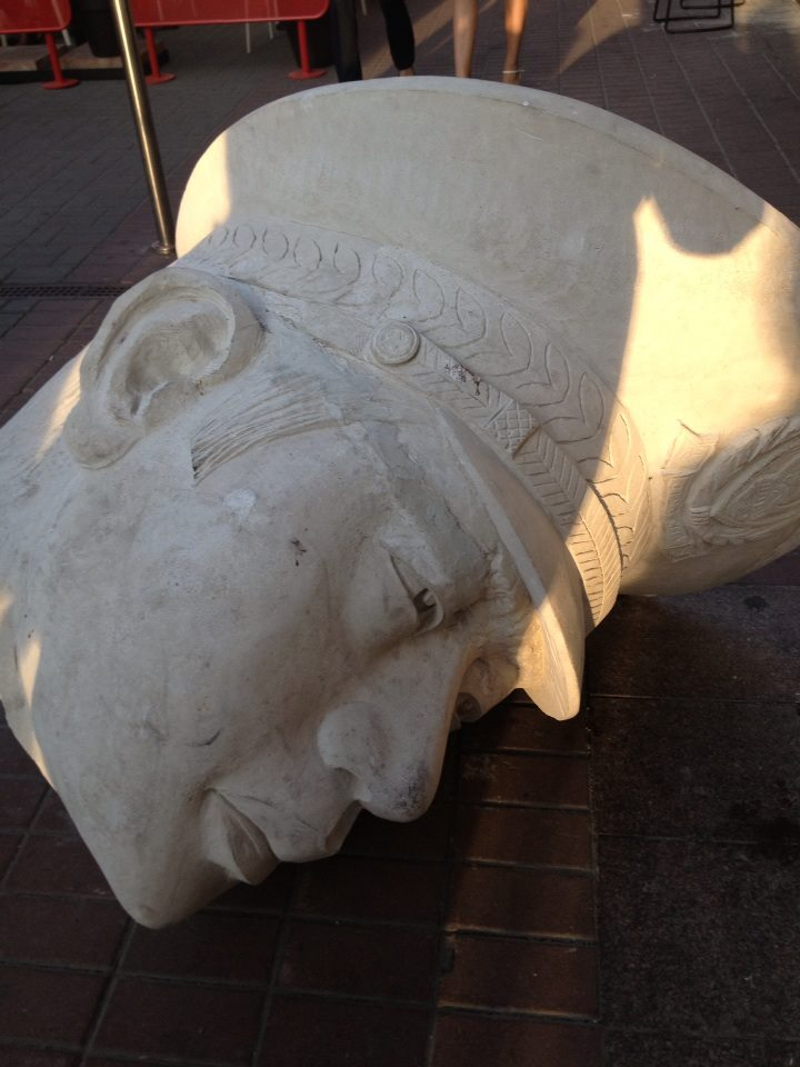 The severed head of a nameless and fictional dictator's statue lies on the sidewalk, greeting all visitors to the museum's entrance.